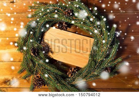 christmas, decoration, holidays and advertisement concept - close up of natural green fir branch wreath and wooden board