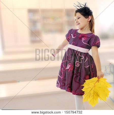 Caucasian little girl dressed in brown dress. She is holding a bouquet of maple leaves. Turning sideways to the camera. In the class where there are school desks.