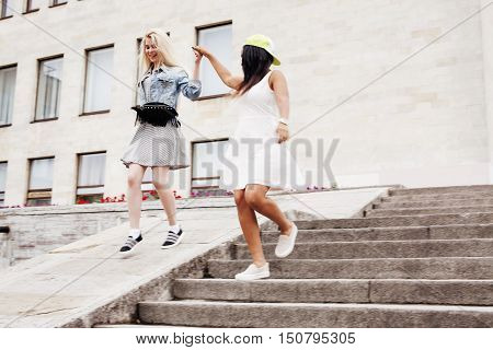 Two teenage girls infront of university building smiling, having fun, lifestyle people concept, diverse nations