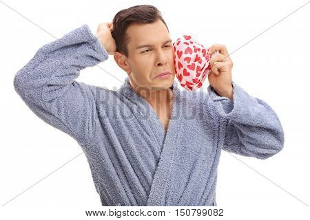 Young man experiencing a toothache and holding an icepack isolated on white background