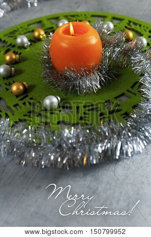 Merry Christmas greeting card made of green christmas mat silver tinsel with silver and golden christmas balls and orange candle against silver background