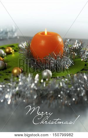 Merry Christmas greeting card made of green christmas mat silver tinsel with silver and golden christmas balls and orange candle against silver background with copy space