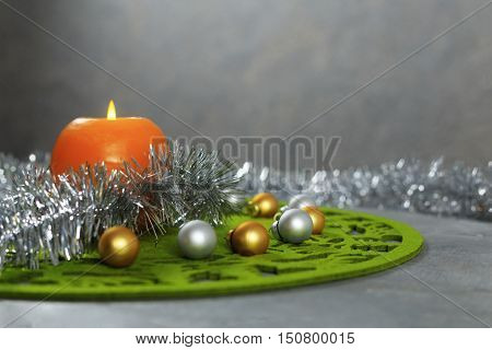 Merry Christmas greeting card made of green christmas mat silver tinsel with silver and golden christmas balls and orange candle against silver background horizontal view with copy space
