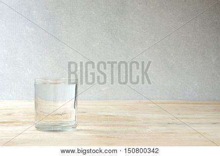 glass of purified water on wooden table - concrete wall background