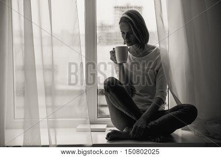 beautiful woman sitting cross-legged, black and white, fall blues concept