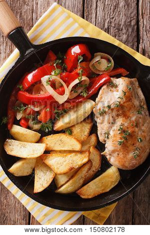 Spicy Chicken With Fried Potatoes And Warm Salad Of Peppers Closeup. Vertical Top View