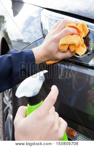 Close Up Of Hand Polishing Car Headlight Using Cloth