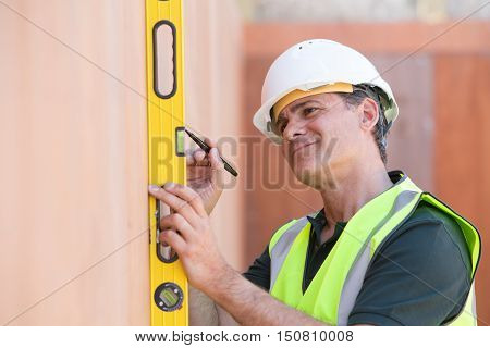 Builder On Site Measuring With Spirit Level