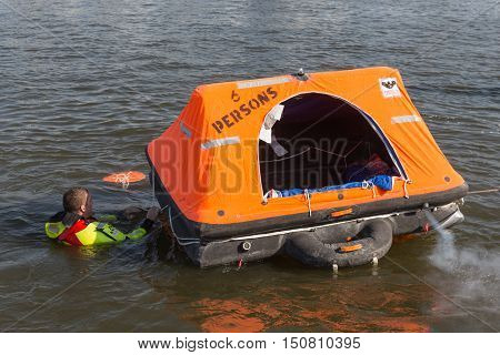 URK THE NETHERLANDS - SEP 24: Rescue worker showing how to use a life raft on September 24 2016 in the harbor of Urk the Netherlands