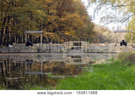 Trees oaks birches with yellow orange green dry leaves green grass a stone bridge with two black metal guns reflected in the water source of the don river autumn cloudy day Children's Park city of Novomoskovsk Russia