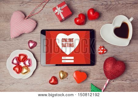 Online dating cocept with digital tablet mock up and heart chocolates. Valentine's day romantic celebration. View from above