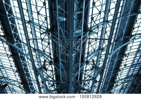 Railway construction canopy. A detail of the glass roof at the railway station blue toning