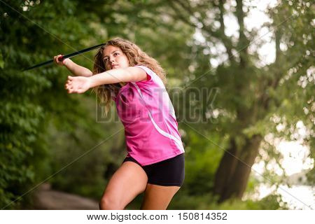 Sporty young woman throwing the javelin practicing her technique in a rural woodland , close up three quarter view