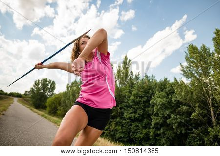 Low angle view of a young woman throwing a javelin during a training session outdoor