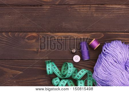 Purple thread crochet , buttons and measuring tape on wooden table. The view from the top. Sewing accessories.