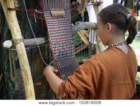 Smolensk, Russia - August 09, 2014: Woman makes cloth on an old loom. Festival of historical reconstruction