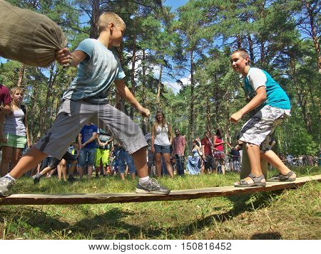 Gnezdovo, Russia - August 09, 2014: Two boys are involved in the Russian national pastime - the fight bags on the board at the historic festival in Gnezdovo