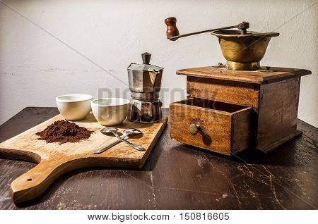 still life with a white two cups and two steel little spoons beside a pile of coffee powder in the background a vintage coffee mill and an old coffee machine