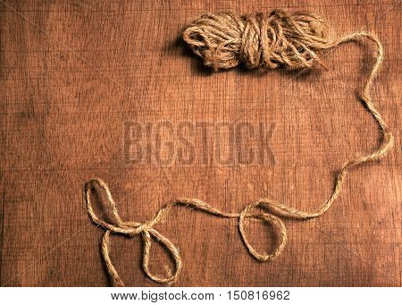 wooden background with a skein of twine
