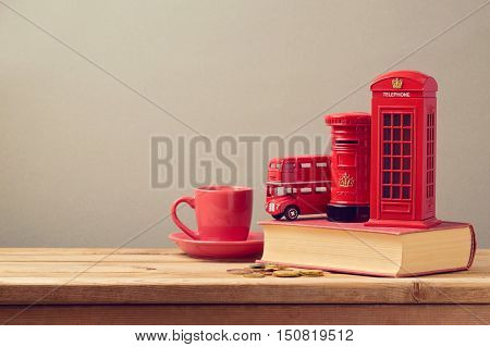 Souvenir money box from trip to London Great Britain on book with coffee cup