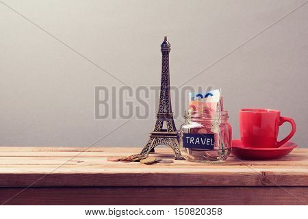 Eiffel Tower souvenir and money box on wooden table. Planning summer vacation money budget trip concept.