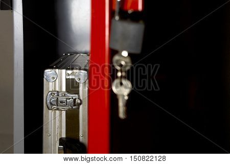 Open door of a metal safe with a briefcase, cropped studio shot, concept of safety or negligence