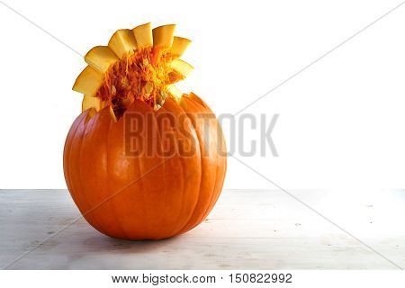 Orange pumpkin cut open with seeds on the lid on light gray wood against a white background copy space