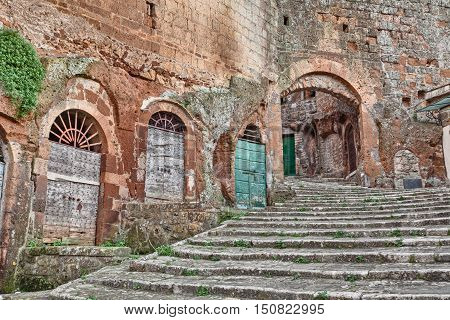 Pitigliano. Tuscany. Italy: old stairway, cellar doors and medieval city door