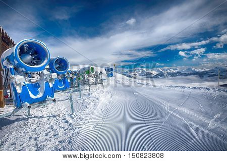Snow cannons with fresh prepared ski slopes with the corduroy pattern in Kitzbuehel ski resort.