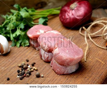 raw fillet medallions of young pork, onions, herbs and fragrant spices on a wooden board