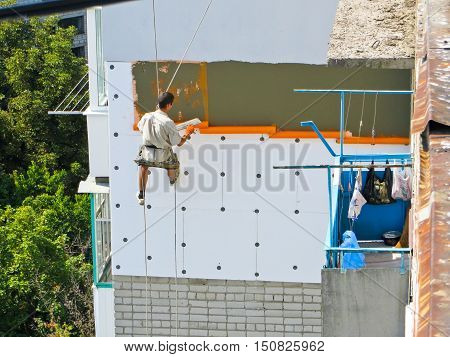 Worker spreading the mortar over the styrofoam. Rope access insulation
