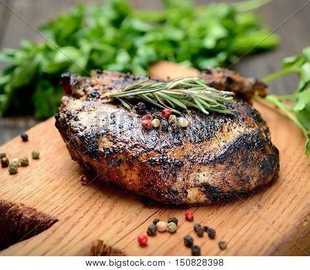 Grilled steak with rosemary, fragrant spices and herbs on a cutting board on a wooden backgroun