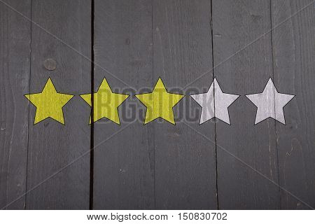 Four yellow ranking stars on black wooden background