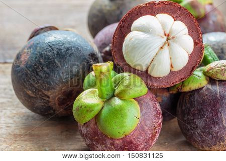 Mangosteen fruit on the ground. Peeled for white meat inside. In Thailand Mangosteen is a fruit that tastes sweet.