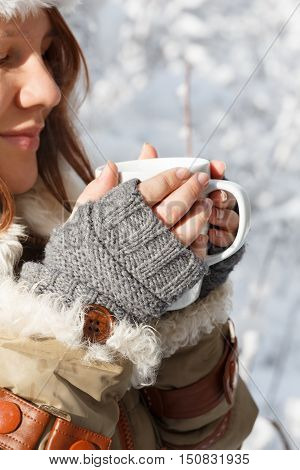 Beautiful young smiling woman in gray fingerless knitted mittens cap and coat with white fur holding in hands white cup of tea or coffee at the background of snowy forest. Closeup.