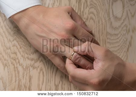 Divorce, separation: hands of man removing wedding or engagement ring, flat lay, top view