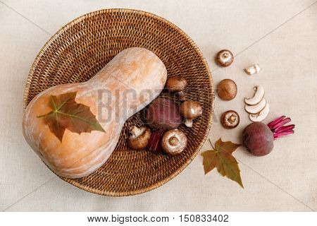 Background from Green Leaves,Purple Beets,Orange Pumpkin,Fresh Mushrooms in the Rattan Braided Big Plate,on the Linen Tablecloth.Autumn Garden's Vegetable Background.Top View