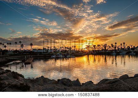 Reflected sunrise clouds in Ventura Marina water at dawn.