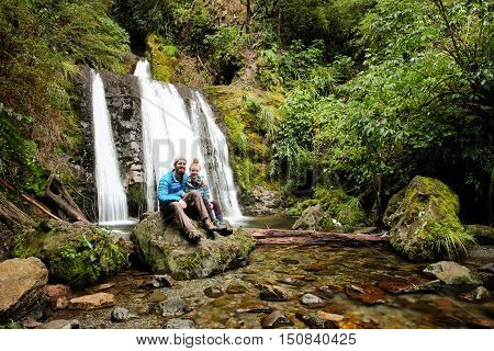 A Happy Couple Poses In Front of a Beautiful Waterfall.  Mt Oxford, Canterbury, New Zealand