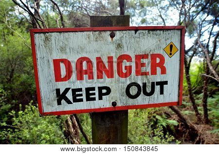 Danger keep out wooden sign panel posted in the wilderness. concept photo of travel and outdoor activity.