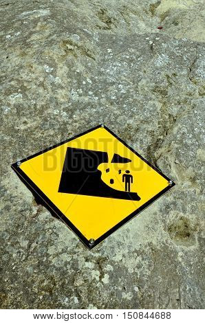 Danger falling rock sign on a cliff wall outdoors.