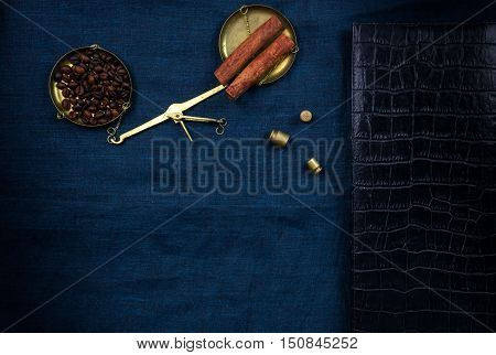 scales with little weights and coffee beans on a blue cloth