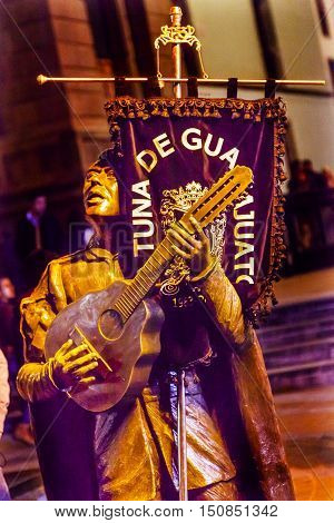 GUANAJUATO, MEXICO - DECEMBER 30, 2014 Troubadour Mariachi Guitar Singer Statue Juarez Theater Night Guanajuato Mexico. Banner of Mariachi Band. Guanajuato location of nightly concerts by Mariachi bands.