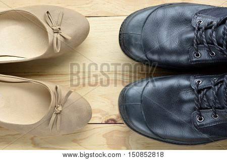 Black Leather Man Shoes Opposite An Elegant Beige Woman Shoes