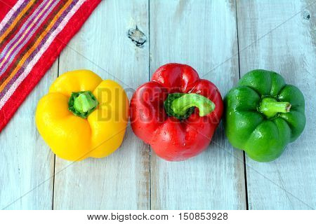 Flat Lay Of A Yellow, Red And Green Capsicum On A Wooden Table