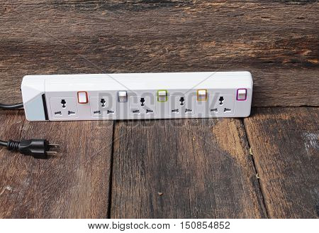 white plug socket electric power bar or extension block on wooden table background and copy space