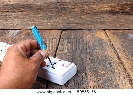 Electric white socket power bar Select focus with shallow depth of field and hand screwdriver skewer in power cord on wooden table background and copy space
