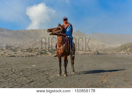 Man is riding horse at Bromo mountain.