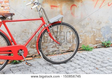 Vintage Red bicycle near the old wall home background.