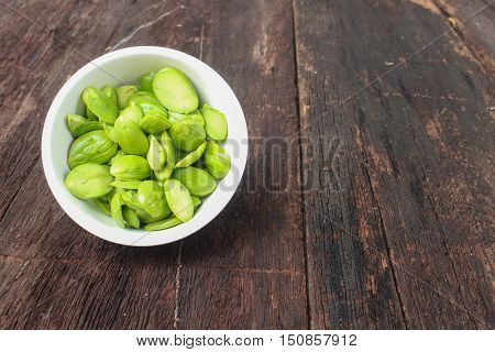 Parkia speciosa in white cup on the wooden floor background ( bean petaitwisted clusterstink bittersato )